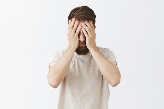 Homme barbu mal à l'aise et triste posant contre le mur blanc