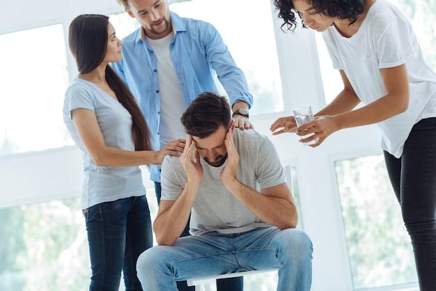 Homme barbu malheureux sans joie tenant ses tempes et se penchant en avant tout en souffrant de migraine