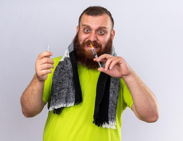 Homme barbu malsain avec une écharpe chaude autour du cou se sentant malade souffrant de la grippe tenant une seringue et une ampoule à l'air inquiet et effrayé