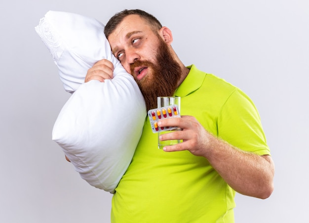 Homme barbu malsain en polo jaune avec oreiller tenant un verre d'eau et des pilules se sentant malade souffrant de grippe debout sur un mur blanc