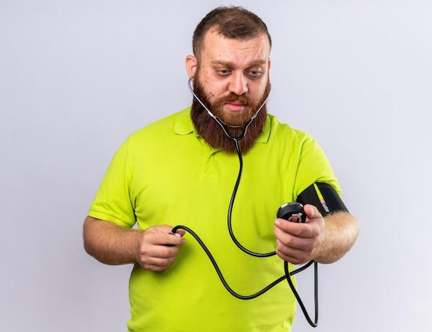 Homme barbu malsain en polo jaune se sentant malade mesurant la pression artérielle à l'aide d'un tonomètre à la colère debout sur un mur blanc