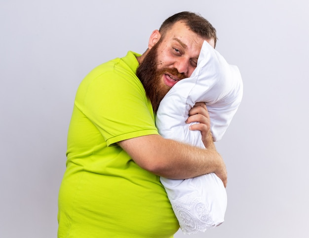 Homme barbu malsain en polo jaune se sentant malade tenant un oreiller souffrant de grippe