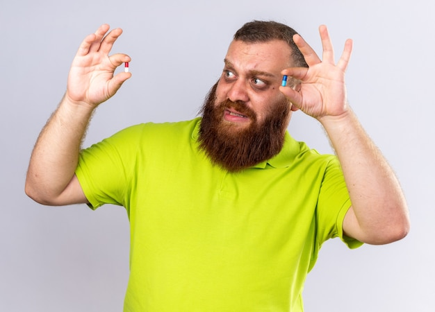 Homme barbu malsain en polo jaune tenant différentes pilules se sentant malade souffrant de grippe ayant l'air confus et effrayé