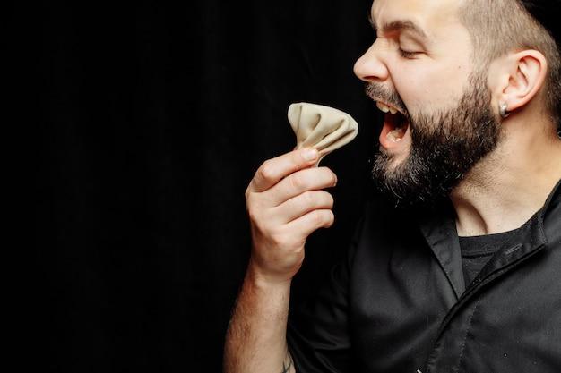 L'homme barbu mange émotionnellement du khinkali. le plat national géorgien khinkali. concept de photo publicitaire de khinkali.