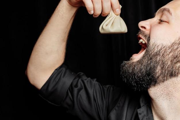 L'homme barbu mange émotionnellement du khinkali. le plat national géorgien khinkali.