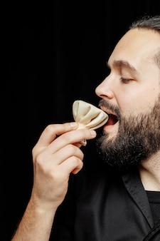 L'homme barbu mange émotionnellement du khinkali