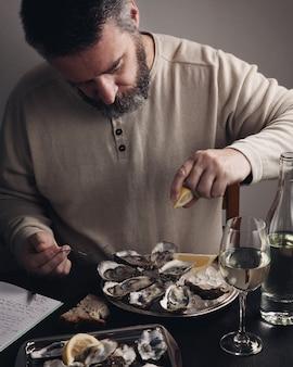 Homme barbu mangeant des huîtres