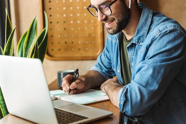 Homme barbu masculin portant des lunettes écrivant des notes et utilisant un ordinateur portable tout en travaillant dans un café à l'intérieur