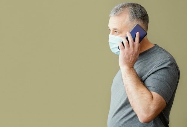 Homme barbu avec masque chirurgical à l'aide de téléphone