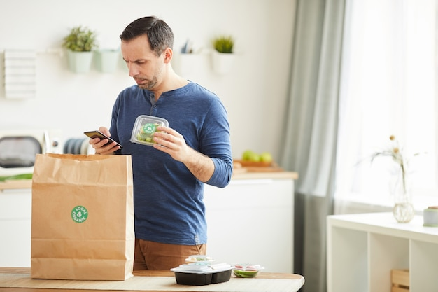 Homme barbu mature à l'aide de smartphone lors du déballage du sac de livraison de nourriture dans l'intérieur de la cuisine