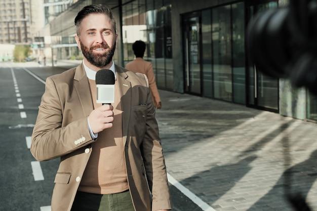 Homme barbu mature parlant au microphone et souriant à la caméra lors de la diffusion en direct sur la rue de la ville