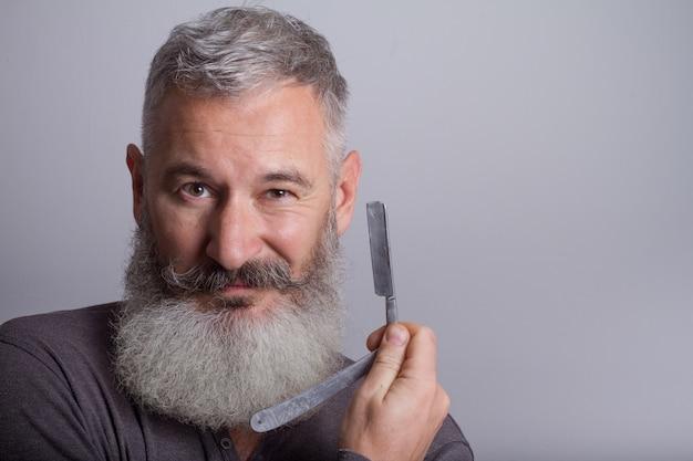 Homme barbu mature avec un rasoir rétro