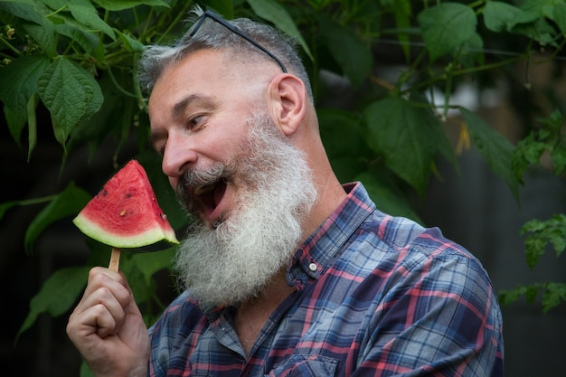 Homme barbu mature avec une tranche de pastèque