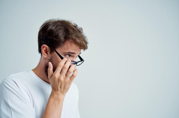 Homme barbu avec une mauvaise vue des problèmes de santé fond clair. photo de haute qualité