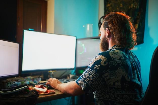 Homme barbu méconnaissable utilisant un ordinateur avec 2 écrans