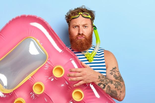 Un homme barbu mécontent pose avec un matelas pneumatique rose, porte des lunettes de natation et un masque de plongée