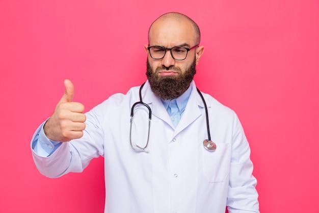 Homme barbu médecin en blouse blanche avec stéthoscope autour du cou portant des lunettes à côté avec un visage sérieux montrant les pouces vers le haut