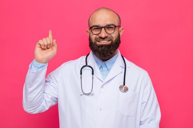 Homme barbu médecin en blouse blanche avec stéthoscope autour du cou portant des lunettes regardant la caméra heureux et positif souriant joyeusement montrant l'index debout sur fond rose