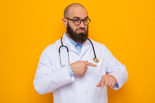 Homme barbu médecin en blouse blanche avec stéthoscope autour du cou portant des lunettes regardant pointant avec le doigt atm sa main rappelant le temps