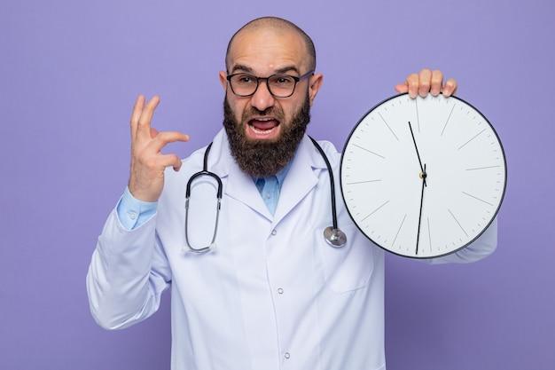 Homme barbu médecin en blouse blanche avec stéthoscope autour du cou portant des lunettes tenant une horloge regardant de côté en criant et en criant se déchaîner le bras debout sur fond violet