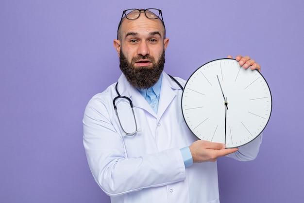 Homme barbu médecin en blouse blanche avec stéthoscope autour du cou tenant une horloge regardant la caméra avec le sourire sur le visage debout sur fond violet