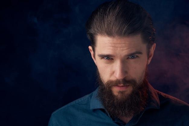 Homme barbu mignon en chemise style élégant close-up sombre.