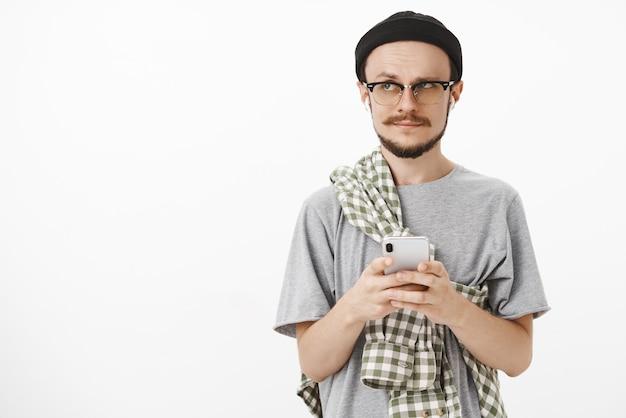 Homme barbu mignon interrogé artistique en bonnet noir et chemise croisée sur la poitrine tenant un smartphone en levant les sourcils tout en regardant à gauche avec une musique d'écoute confuse dans des écouteurs sans fil