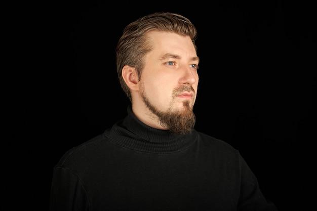 Homme barbu mignon, portrait de demi-profil, fond noir. jeune homme en pull col polo noir. homme confiant et réussi.