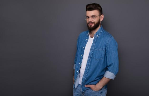 Homme barbu moderne et intelligent confiant dans des vêtements en denim décontractés et des lunettes pose