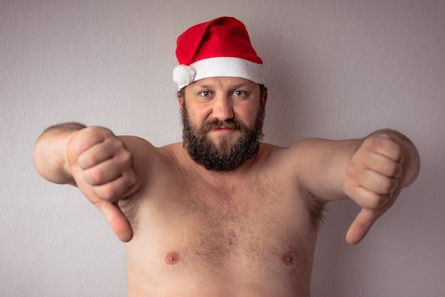 Homme barbu à moitié nu avec chapeau de père noël montrant les pouces vers le bas contre un mur gris