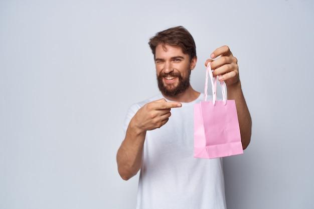 Homme barbu montrant le mode de vie cadeau paquet rose. photo de haute qualité