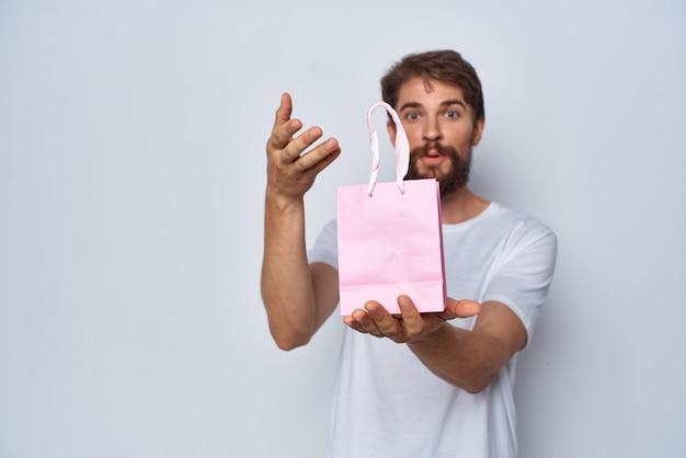 Homme barbu montrant le style de vie cadeau paquet rose