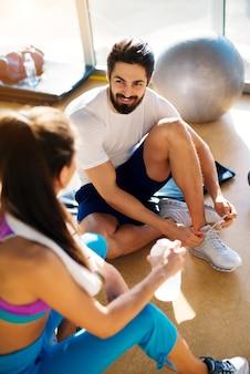 Un homme barbu musclé attache ses lacets sur des baskets à la salle de sport tout en parlant avec une fille à côté de lui.