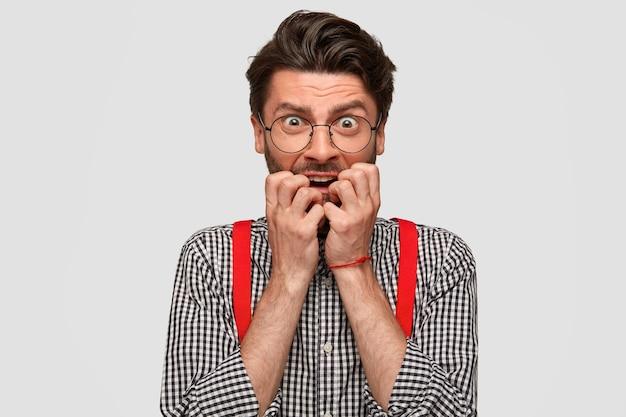 Un homme barbu nerveux se mord les ongles et regarde avec anxiété, a une expression perplexe, a peur de quelque chose