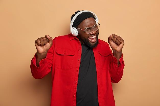 Un homme barbu noir ravi lève les poings fermés, chante une chanson à haute voix, danse