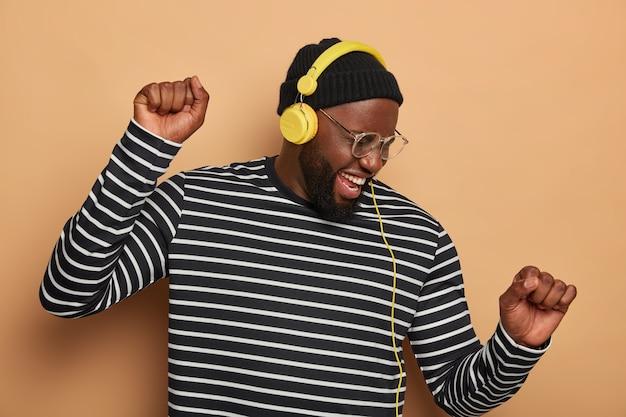 Un homme barbu noir ravi se déplace au rythme de la musique, porte des lunettes transparentes