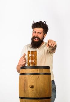 L'homme barbu de l'oktoberfest avec un verre de bière pointe vers l'avant, nous rencontrons l'homme des traditions de l'oktoberfest en allemagne