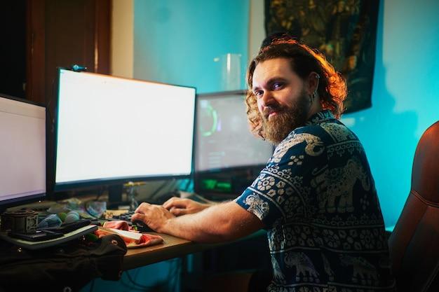 Homme barbu avec ordinateur et 2 écrans regardant et souriant à la caméra