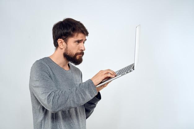 Homme barbu avec ordinateur portable en mains sur fond clair
