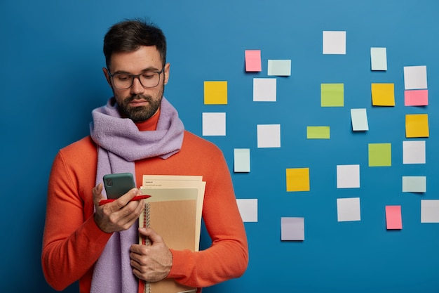 Homme barbu organisant ses tâches à l'aide de notes autocollantes