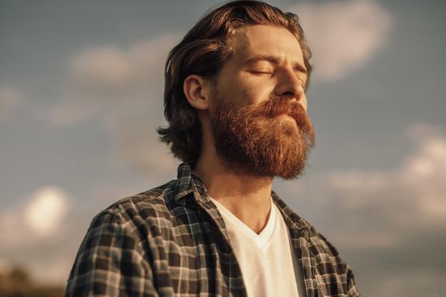 Homme barbu pacifique tenant les yeux fermés contre le ciel nuageux