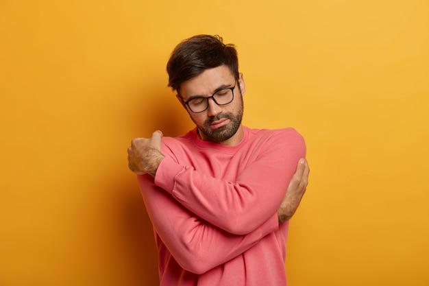 Un homme barbu paisible croise les mains sur le corps, se sent réconforté dans son nouveau pull