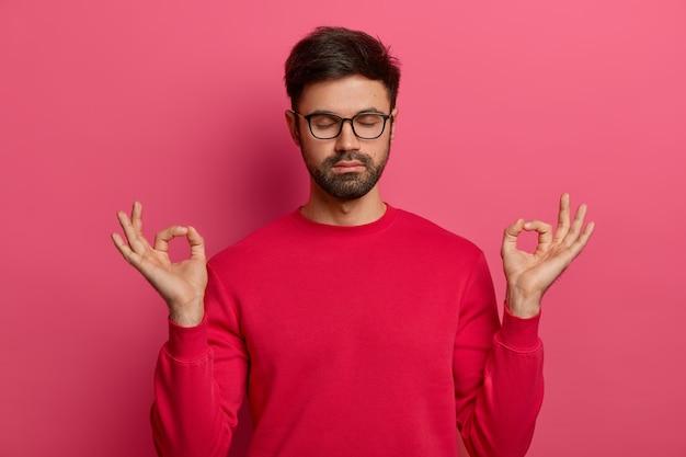 Un homme barbu paisible pratique le yoga, médite avec un geste zen