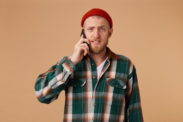 Homme barbu parlant sur un téléphone mobile