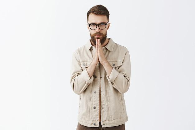 Homme barbu patient dans des verres posant contre le mur blanc