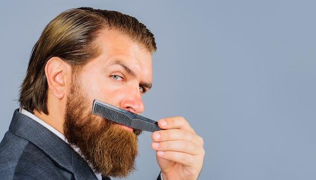 Homme barbu avec peigne de coiffeur. salon de coiffure. soin de barbe professionnel. coiffeur. salon pour hommes. espace de copie pour la publicité du salon de coiffure.