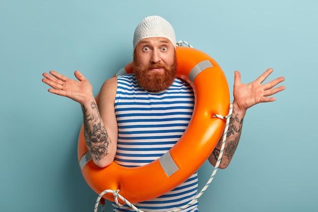 Un homme barbu perplexe écarte les mains avec le doute, porte un chapeau de bain blanc, porte une bouée de sauvetage