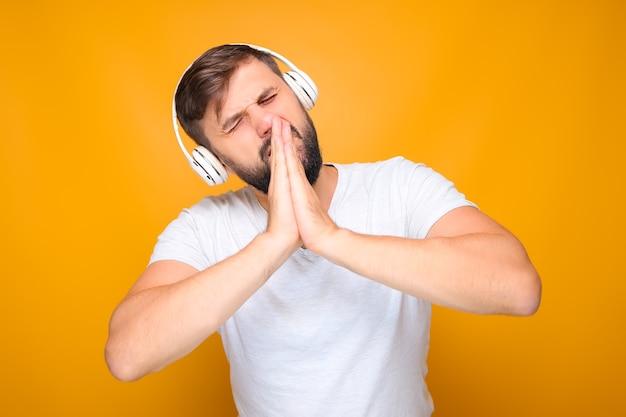 L'homme barbu a plié ses paumes devant son visage et écoute de la musique émotionnelle.