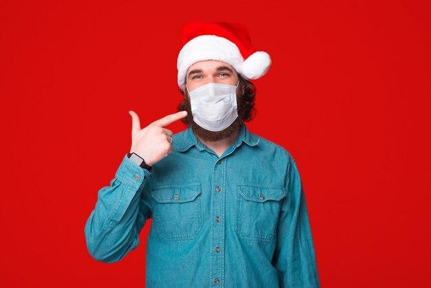 Homme barbu portant un chapeau de noël et pointant sur son masque médicinal, soyez en sécurité sans zone de covid