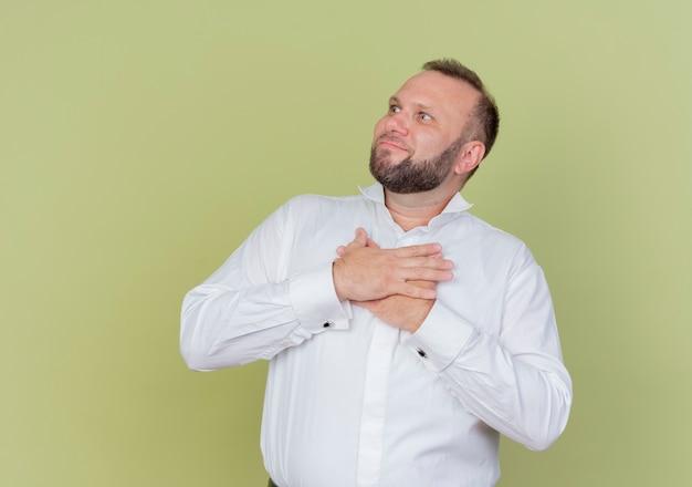 Homme barbu portant une chemise blanche à côté tenant les mains sur la poitrine se sentant reconnaissant debout sur un mur léger